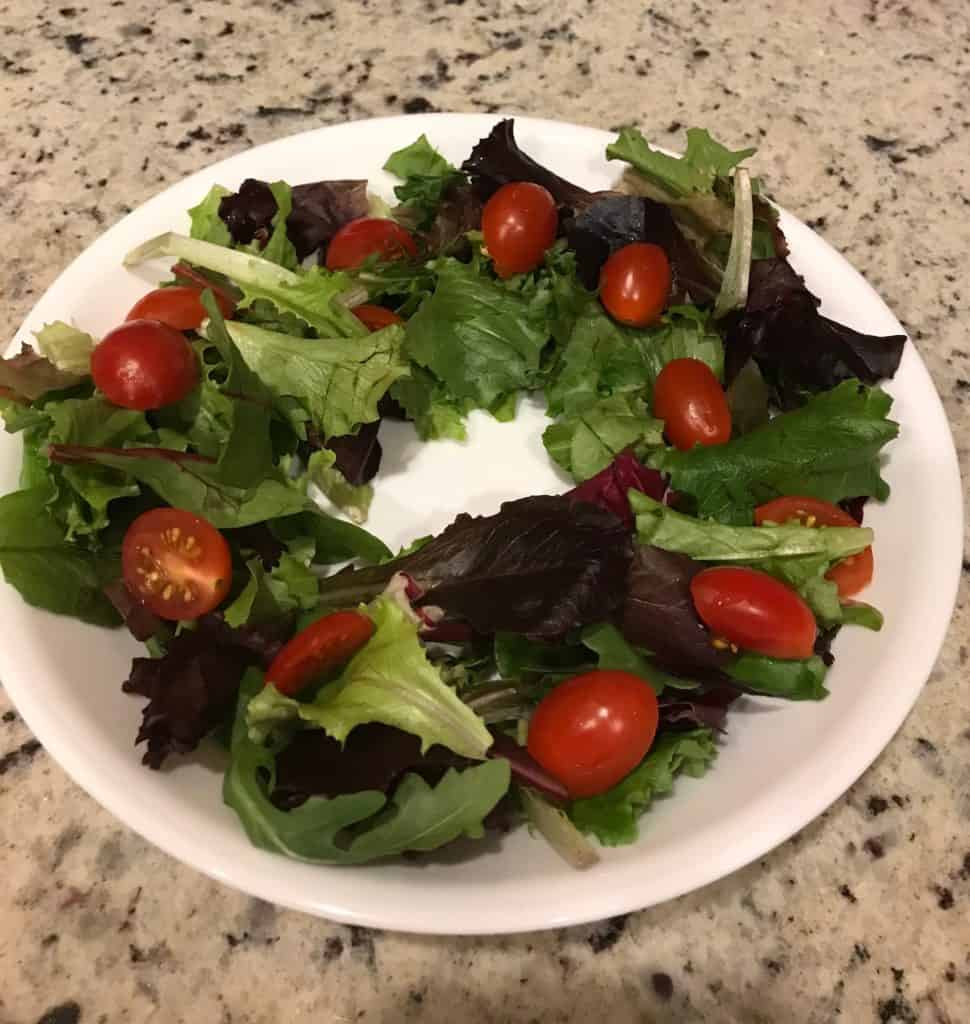 Ring of mixed salad greens and cherry tomato halves