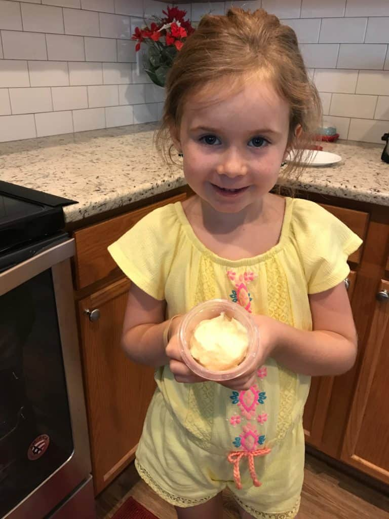 Making memories and teaching southern manners to my granddaughter holding a bowl of homemade butter.