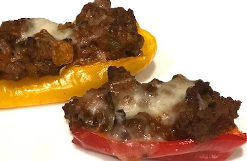 Red and yellow mini peppers stuffed with ground beef and topped with melted cheese