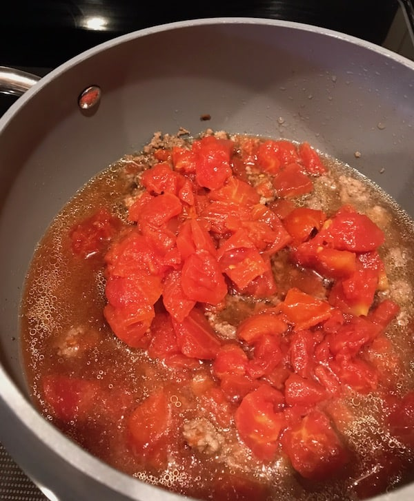 Diced tomatoes in the pot with the chopped ground beef