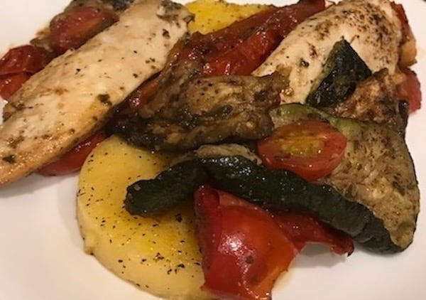 Polenta on a plate and smothered with chicken, vegetables, and seasonings