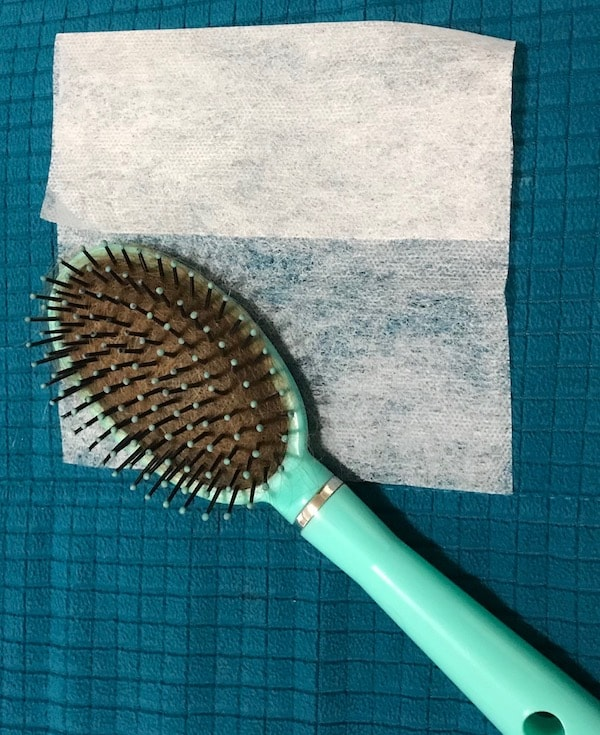 Hairbrush on top of a dryer sheet