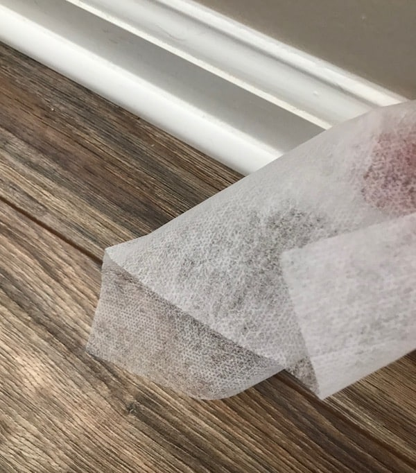 Dryer sheet wiping a baseboard