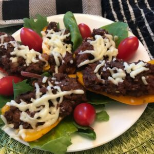 Mini Stuffed Peppers on a plate with lettuce and tomatoes