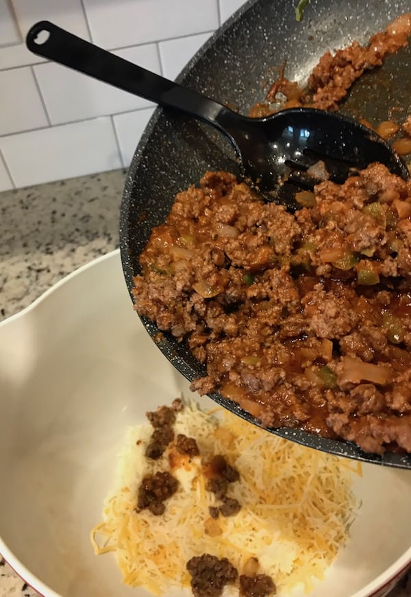 Pouring ground beef mixture into a bowl with the shredded cheese