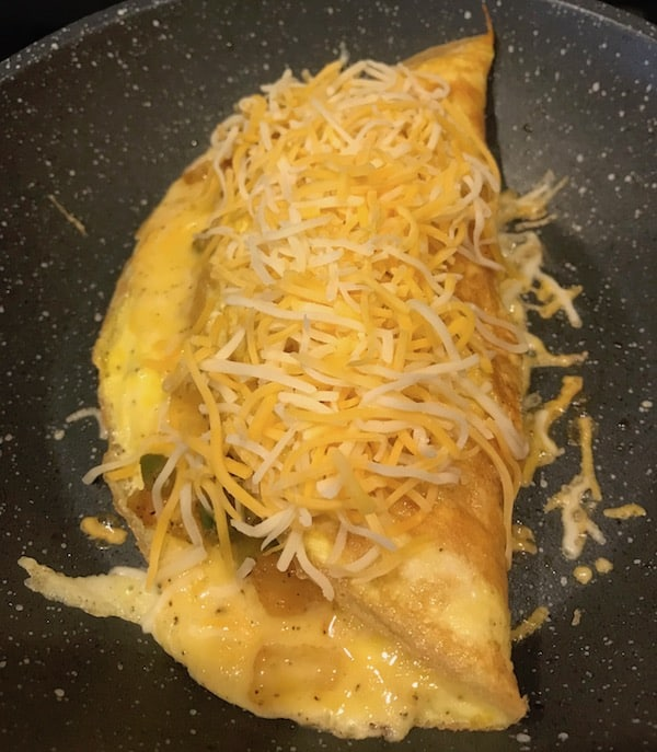 Vegetable omelet topped with more shredded cheese