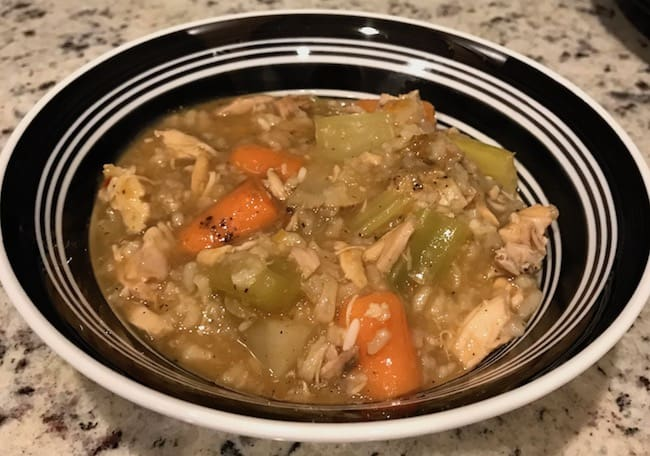Bowl of cooked Crockpot chicken stew with vegetables, rice, and broth