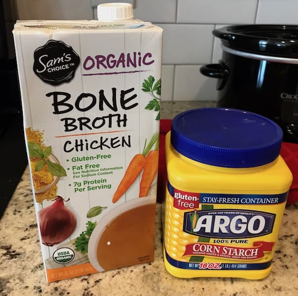 Carton of chicken bone broth and container of cornstarch to thicken the broth for the Crockpot chicken stew