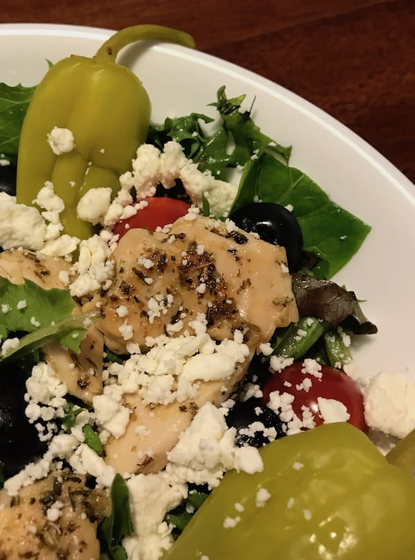 Mediterranean salad with lettuce, tomatoes, olives, chicken, pepperoncini, and feta cheese