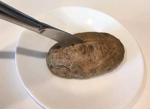 Cut the spud lengthwise with a knife.