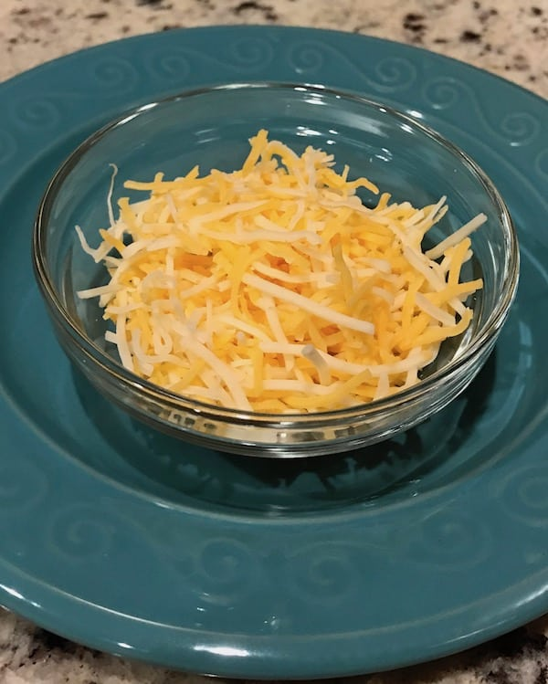 Shredded cheese in clear glass bowl on teal plate