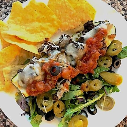 Zucchini boat stuffed with ground beef, cheese, salsa, olives, and jalapeños on a bed of lettuce and served with corn chips
