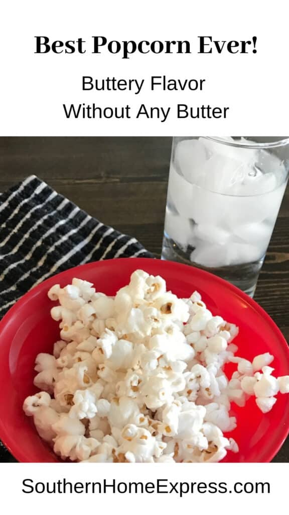 Bowl of popcorn with glass of ice water and a black and white towel.