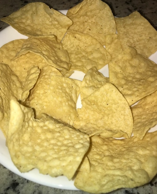 Line a bowl with nacho chips.