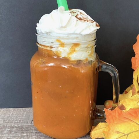 Pumpkin pie smoothie and whipped cream in a glass mug