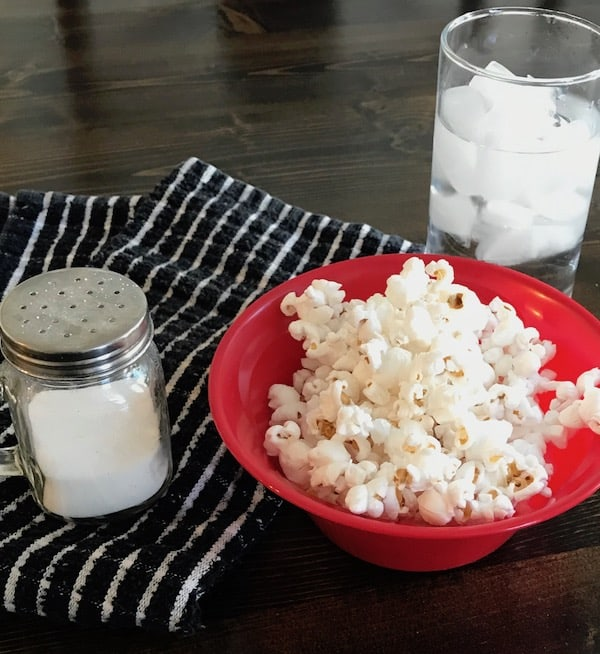 Bowl of popcorn with salt shaker and glass of ice water