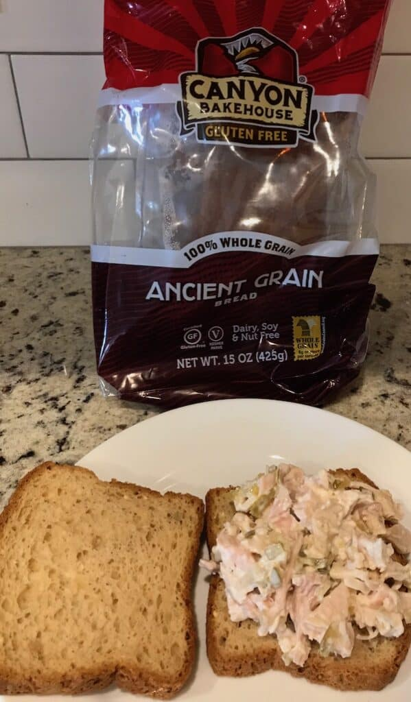 Chicken salad on a slice of bread with a loaf of gluten-free bread behind it