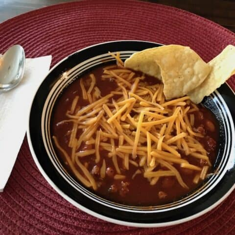 Chili topped with cheese and a side of chips