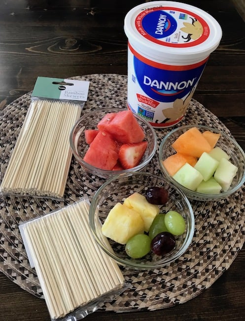 Skewers, bowls of fruit, and a container of yogurt
