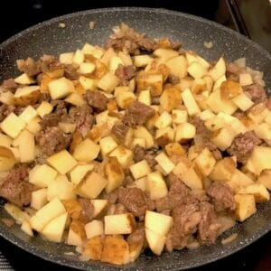 Steak, onions, and potatoes in a skillet
