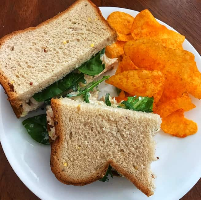 Chicken salad sandwich and barbecue potato chips on a plate