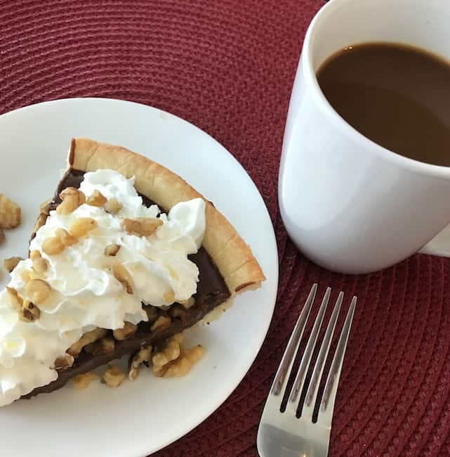 Slice of chocolate walnut pie and a cup of coffee