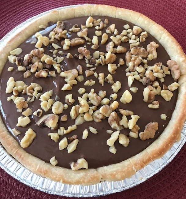 Chocolate pie with chopped walnuts pressed into the top