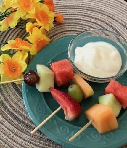 Fruit on a skewer next to a bowl of vanilla yogurt