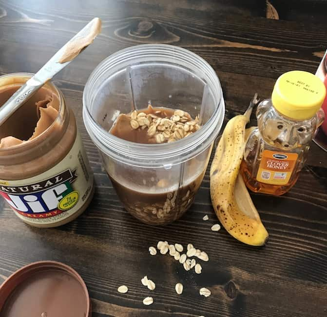 Open jar of peanut butter, banana peel, honey, and blender filled with ingredients
