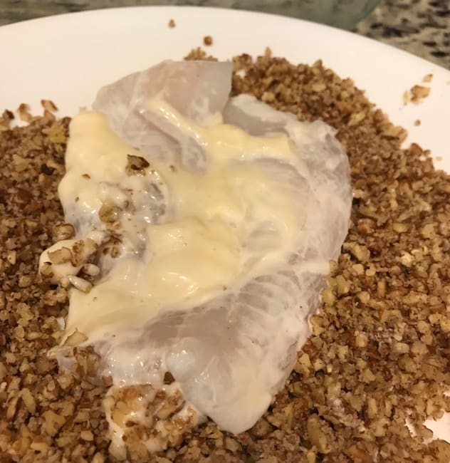 Rolling the mayonnaise coated fish in crushed pecans