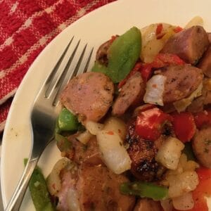 Sausage and peppers on a plate with a fork