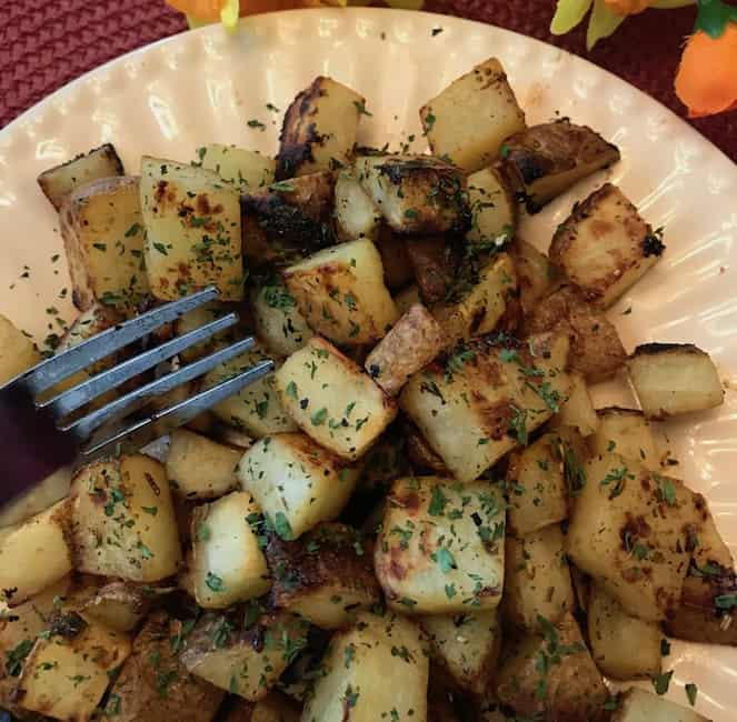 Honey mustard roasted potatoes on a plate with a fork.