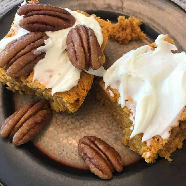 2 pieces of pumpkin cake with icing--one with pecans and one without