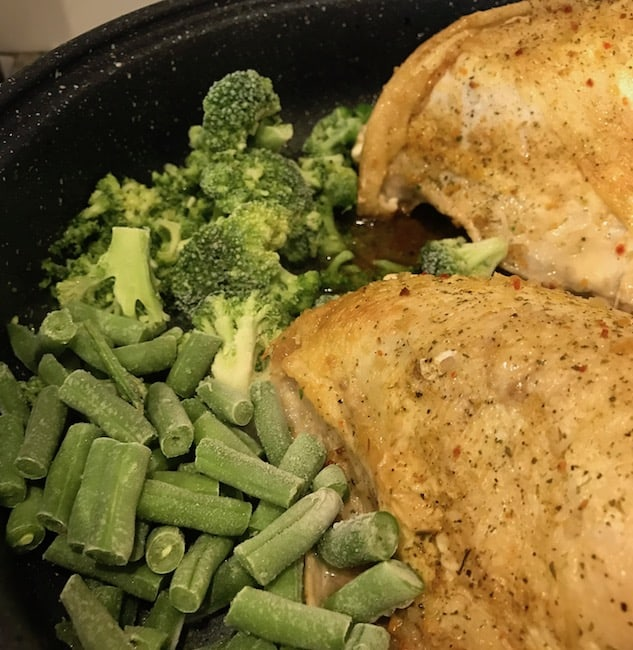 Green beans and broccoli with chicken in a pan