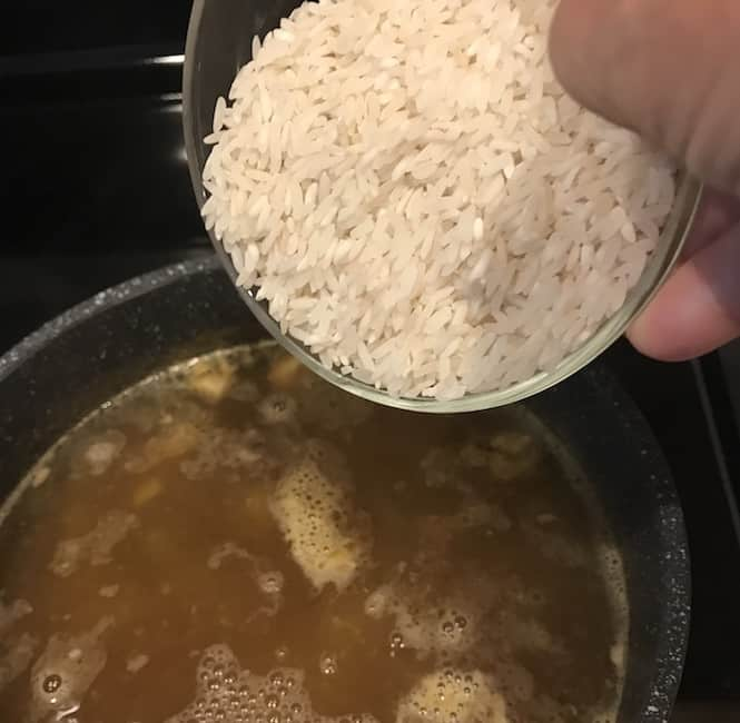 Adding rice to the pot of soup
