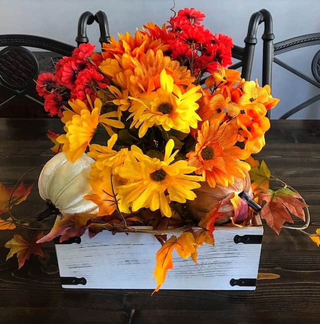 Centerpiece with flowers, velvet pumpkins, stands of leaves, and a distressed white wooden box.