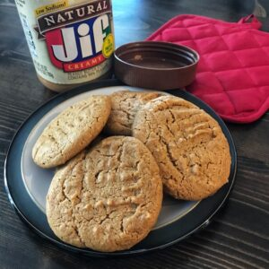 Gluten-free peanut butter cookies, jar of peanut butter, and potholder