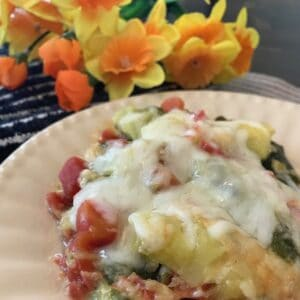 Zucchini tomato casserole on a plate beside yellow flowers