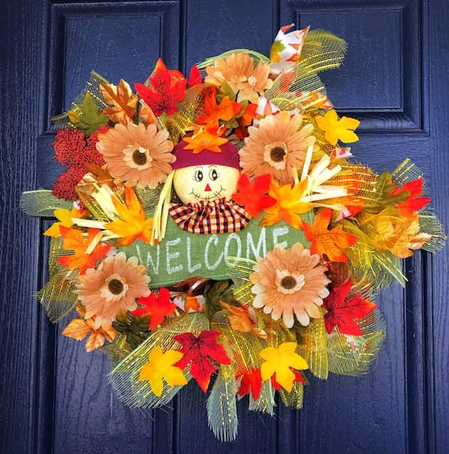 Autumn wreath with flowers and a scarecrow.