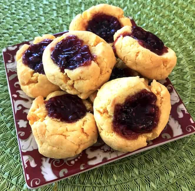 Baked raspberry thumbprint cookies stacked on a plate.