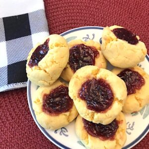 Raspberry thumbprint cookies on a plate beside a napkin