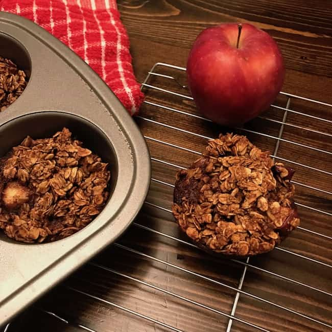 Apple oat muffin cooling on a rack beside an apple