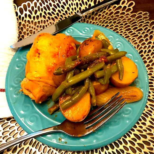 Slow cooker chicken and vegetable dinner on a plate with a fork and knife
