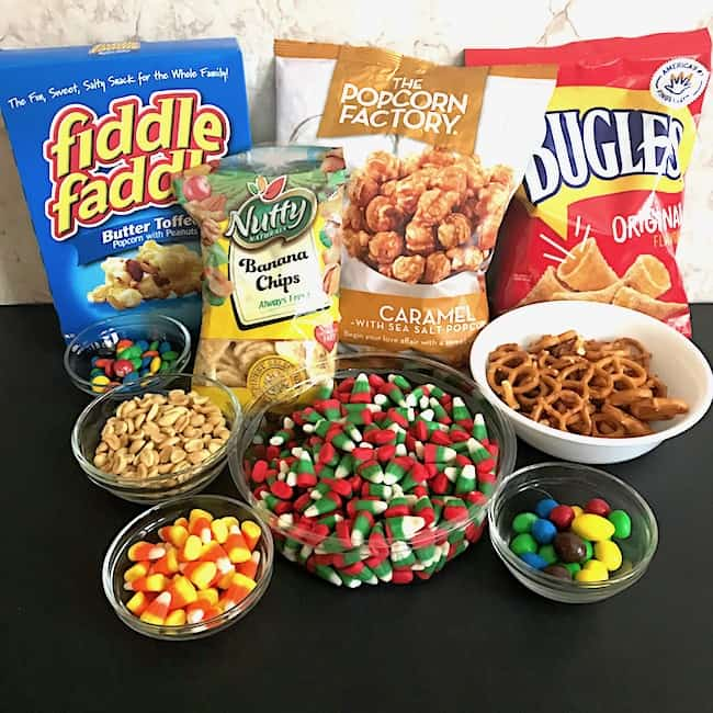 Sweet and salty snack mix ingredients, including toffee popcorn, caramel corn, bugles, banana chips, pretzels, peanuts, candy corn, and M&Ms