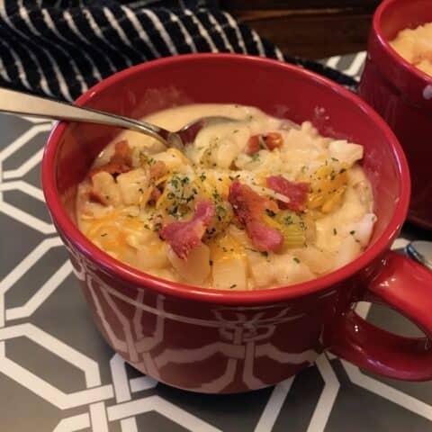 Mug of potato soup with bacon and cheese