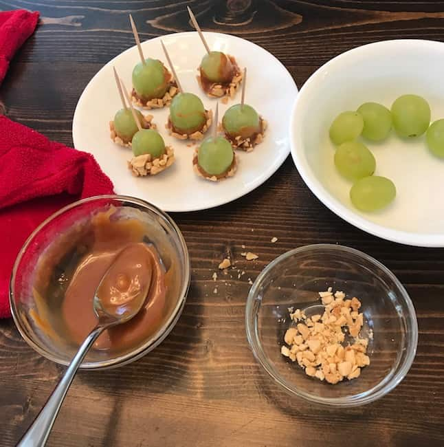 Assembly line of caramel apple grape ingredients with bowls of grapes, caramel, and nuts