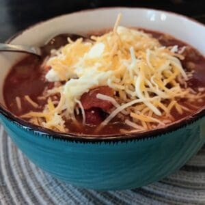Chili in a bowl and topped with sour cream and shredded cheese