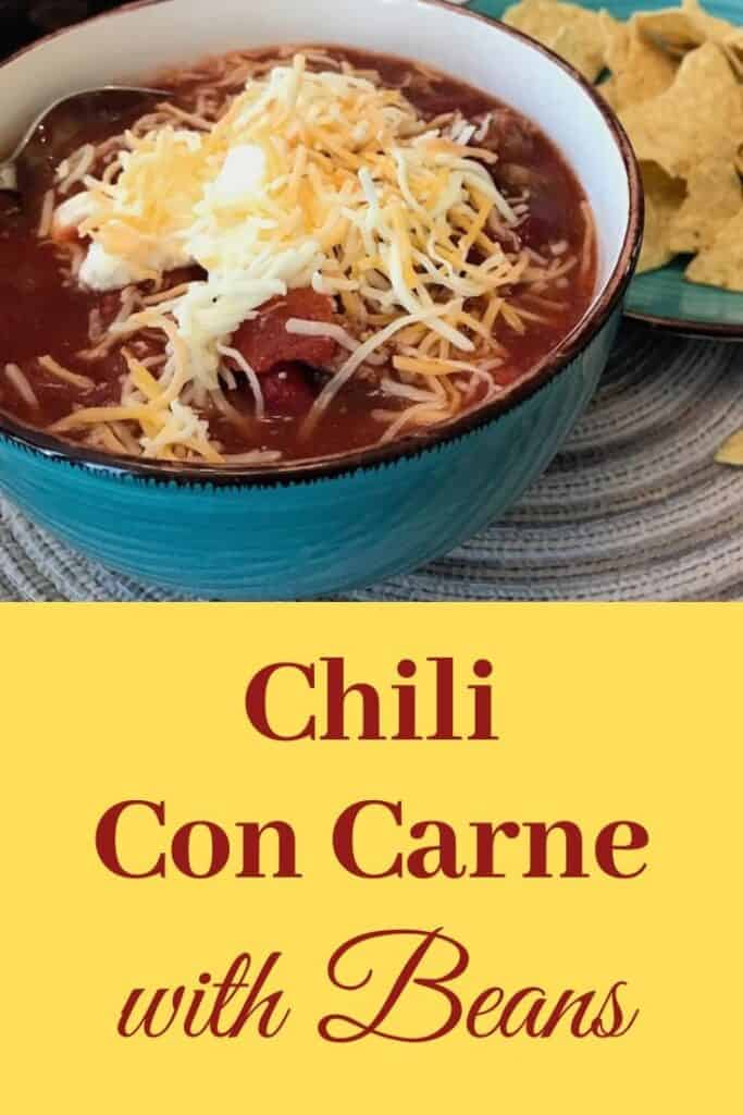 Bowl of chili con carne with sour cream and cheese beside a plate of chips