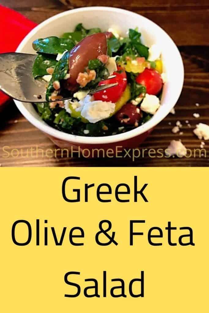 Fork holding a bit of Greek feta and olive salad