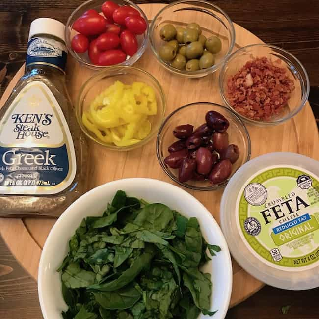 Spinach, tomatoes, pepper rings, green olives, kalamata olives, bacon bits, feta cheese, and Greek salad dressing